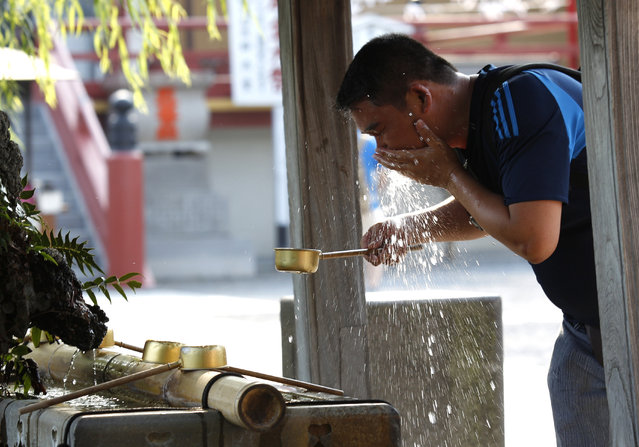 A tourist washes his face to cool off at Bentendo Temple  in Tokyo's Ueno Park, Monday, July 27, 2015. As temperatures rose, many locals and tourists alike came to the park to escape from the heat. (Photo by Ken Aragaki/AP Photo)
