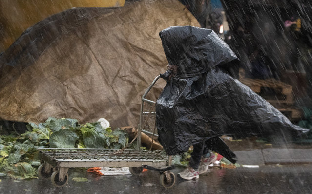 A man shelters from the rain with  plastic bags, at a market in Tembisa, east of Johannesburg, South Africa, Monday, March 23, 2020. South Africa, Africa's most industralized economy and a nation of 57 million people, will to go into a nationwide lockdown for 21 days from Thursday to fight the spread of the new coronavirus. (Photo by Themba Hadebe/AP Photo)