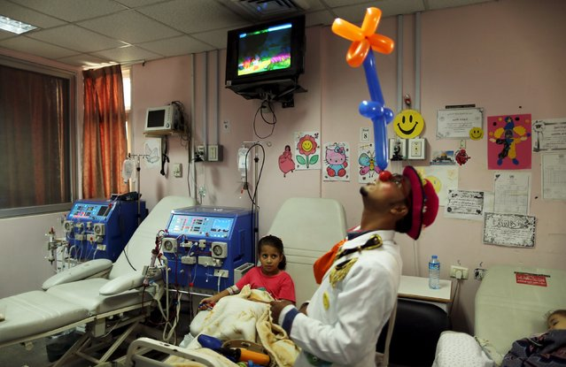 A Palestinian social activist working for the International South South Cooperation (Cooperazione Internazionale Sud Sud, or CISS) entertain children suffering from kidney failure, inside a hospital in Gaza City August 31, 2015. (Photo by Mohammed Salem/Reuters)