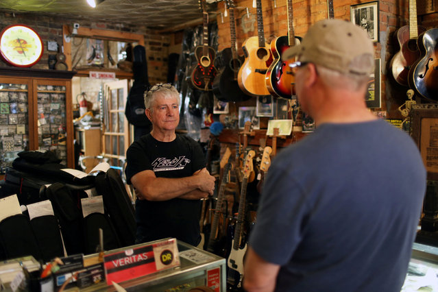Rick Kelly, owner of Carmine Street Guitars, speaks to a customer at his shop in New York City, U.S., July 21, 2016. (Photo by Joe Penney/Reuters)
