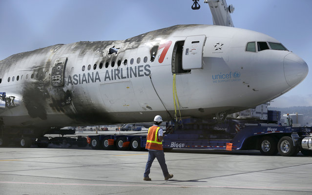 In this July 12, 2013, file photo, a man looks at the wreckage of Asiana Flight 214 at San Francisco International Airport in San Francisco. An attorney overseeing lawsuits stemming from a fatal plane crash in San Francisco four years ago says the last remaining suit in the U.S. has been settled. Ronald Goldman said his client, Kyung Rhan Rha, reached a deal with Asiana Airlines on Thursday, September 21, 2017, just as her case was headed for trial. The terms of the settlement were confidential. (Photo by Jeff Chiu/AP Photo)