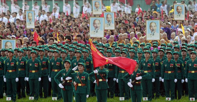 Attendees sing the national anthem in front of portraits of late Vietnamese revolutionary leader Ho Chi Minh during a parade marking their 70th National Day at Ba Dinh square in Hanoi, Vietnam September 2, 2015. (Photo by Reuters/Kham)