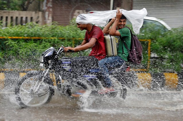 Commuters use a plastic sheet to take shelter from rain as they ride through a waterlogged road in Ahmedabad, India, July 27, 2016. (Photo by Amit Dave/Reuters)