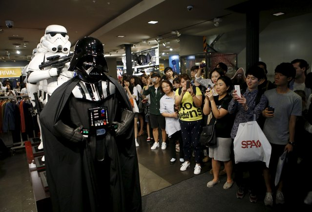 """Visitors take photographs of a worker dressed as Darth Vader from """"Star Wars"""" at Myeongdong shopping district in Seoul, South Korea, September 4, 2015. (Photo by Kim Hong-Ji/Reuters)"""