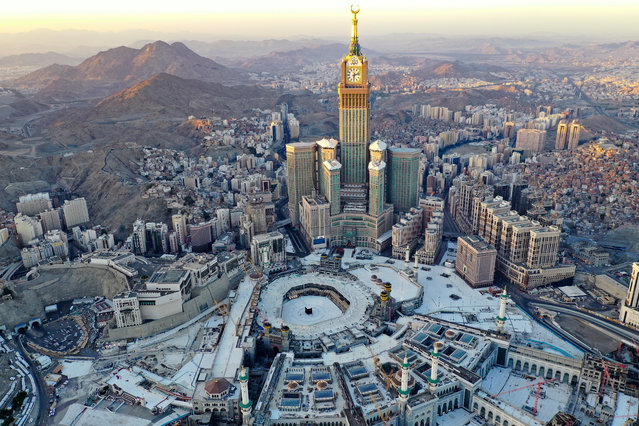 An aerial view shows the Grand Mosque and the Mecca Tower,  deserted on the first day of the Muslim fasting month of Ramadan, in the Saudi holy city of Mecca, on April 24, 2020, during the novel coronavirus pandemic crisis. (Photo by Bandar Aldandani/AFP Photo)