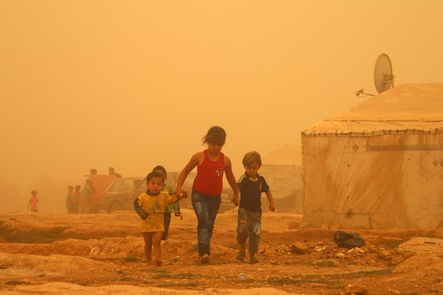 Syrian children walk amid the dust during a sandstorm on September 7, 2015 at a refugee camp on the outskirts of the eastern Lebanese city of Baalbek. (Photo by AFP Photo/Stringer)
