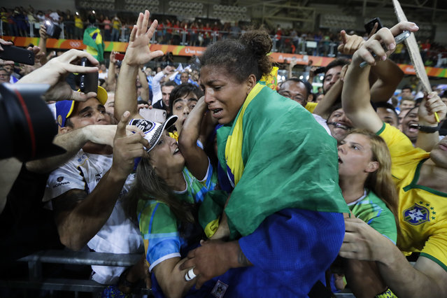 Brazil's Rafaela Silva, centre, celebrates after winning the gold medal of the women's 57-kg judo competition at the 2016 Summer Olympics in Rio de Janeiro, Brazil, Monday, August 8, 2016. (Photo by Markus Schreiber/AP Photo)
