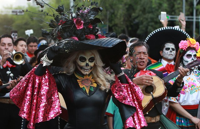 """People participate in the the parade of """"Catrinas"""", in Mexico City, Mexico, 22 October 2017. The Calavera Catrina, or """"Dapper Skeleton"""", is the most representative image of the Day of the Dead, a indigenous festivity that honours ancestors and occurs from 01 to 02 November. (Photo by Mario Guzman/EPA/EFE)"""