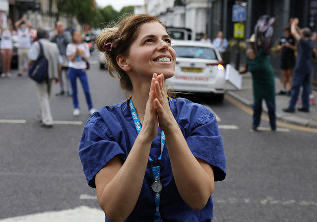 An NHS worker reacts at the Chelsea and Westminster Hospital during the Clap for our Carers campaign in support of the NHS, following the outbreak of the coronavirus disease (COVID-19), London, Britain, May 21, 2020. (Photo by Kevin Coombs/Reuters)