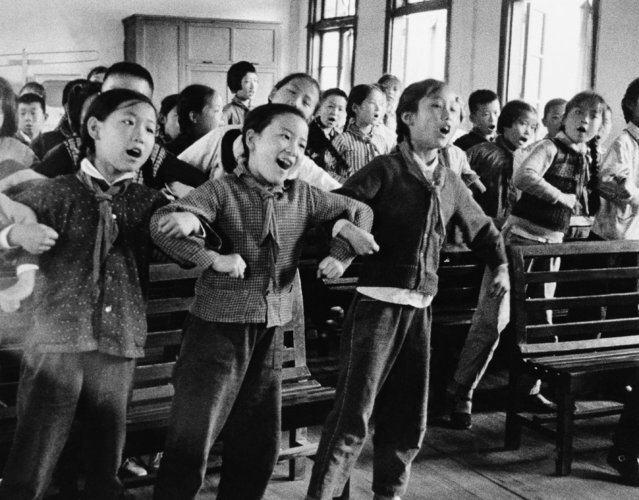 School children swing in unison to group singing in their classroom in Shanghai on September 23, 1966. Their song is based mainly on the writings of Mao Tse-Tung, chairman of the Chinese Communist Party. Such political indoctrination is an important part of the school curriculum. (Photo by AP Photo)