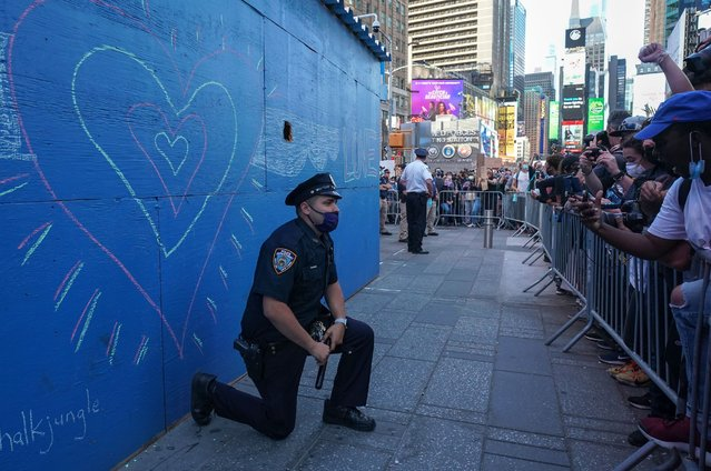 A New York City police officer takes a knee during a demonstration by protesters in Times Square over the death of George Floyd by a Minneapolis police officer at a rally on May 31, 2020 in New York. Thousands of National Guard troops patrolled major US cities  after five consecutive nights of protests over racism and police brutality that boiled over into arson and looting, sending shock waves through the country. The death Monday of an unarmed black man, George Floyd, at the hands of police in Minneapolis ignited this latest wave of outrage in the US over law enforcement's repeated use of lethal force against African Americans – this one like others before captured on cellphone video. (Photo by Bryan R. Smith/AFP Photo)