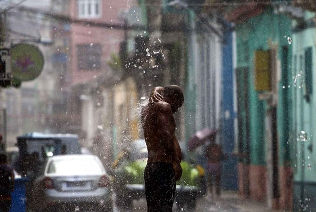 A man takes a shower on a street from water coming from a drainpipe as it rains in Havana, Cuba, Wednesday, July 27, 2016. During the last couple of weeks short but intense tropical downpours have been coming down of Havana every afternoon. (Photo by Desmond Boylan/AP Photo)
