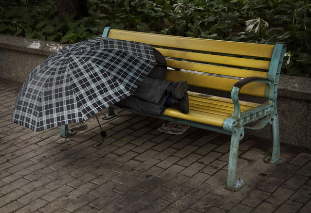 A Chinese man uses an umbrella to shield himself from the rain as he sleeps on a park bench on September 1, 2014 in Beijing, China. (Photo by Kevin Frayer/Getty Images)
