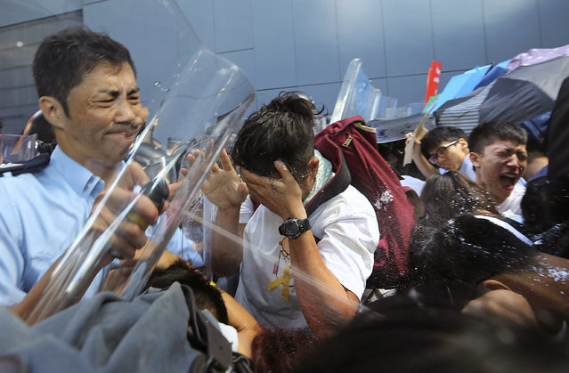 Riot policemen use pepper spray to young pro-democracy activists who forced their way into Hong Kong government headquarters during a demonstration in Hong Kong, early Saturday, September 27, 2014. The scenes of disorder came at the end of a weeklong strike by students demanding China's communist leaders allow residents to directly elect a leader of their own choosing in 2017. (Photo by AP Photo/Apple Daily)
