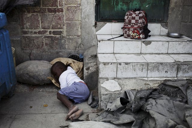 A boy takes a nap on a street in Port-au-Prince, Haiti, February 24, 2016. (Photo by Andres Martinez Casares/Reuters)
