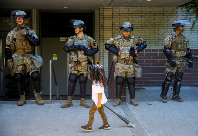A child carrying a small broom walks by a line of National Guard members deployed to Bellevue Square as community members clean up after looting and vandalism that occurred Sunday at Bellevue Square in downtown Bellevue, Washington, U.S. June 1, 2020. (Photo by Lindsey Wasson/Reuters)