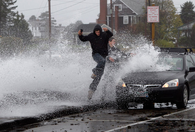 Caleb Lavoie, 17, of Dayton, Maine, front, and Curtis Huard, 16, of Arundel, Maine, leap out of the way as a large wave crashes over a seawall on the Atlantic Ocean during the early stages of Hurricane Sandy in Kennebunk, Maine, on October 29, 2012. (Photo by Robert F. Bukaty/AP Photo)