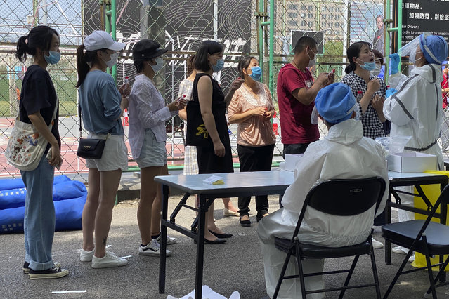 Residents line up to get tested at a coronavirus testing center set up outside a sports facility in Beijing, Tuesday, June 16, 2020. China reported several dozen more coronavirus infections Tuesday as it increased testing and lockdown measures in parts of the capital to control what appeared to be its largest outbreak in more than two months. (Photo by Ng Han Guan/AP Photo)
