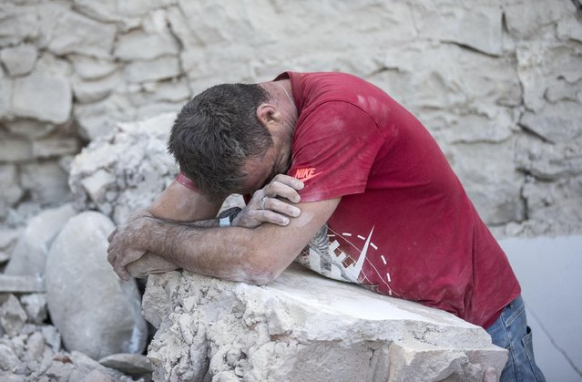 A man crys on the rubble in Amatrice, central Italy, where a 6.1 earthquake struck just after 3:30 a.m., Wednesday, August 24, 2016. (Photo by Massimo Percossi/ANSA)