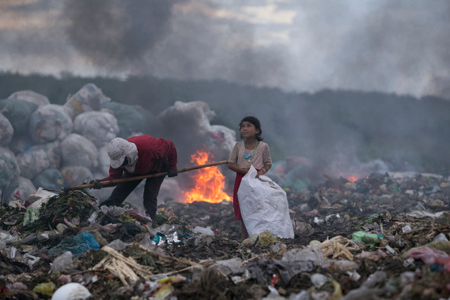 "Winner of Ciwem environmental photographer of the year 2017: Quoc Nguyen Linh Vinh for ""The hopeful eyes of the girl making a living by rubbish"". Vinh's winning photo is a poignant image of a child and her mother collecting waste. Vinh said ""The child was happy, looking at the dark clouds and chatting to her mother. This was so touching. She should have been enjoying her childhood and playing with friends rather than being there"". (Photo by Quoc Nguyen Linh Vinh/2017 Ciwem environmental photographer of the year)"