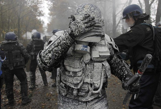 A French riot gendarme reacts after being covered with lime during clashes with demonstrators during an evacuation operation on land that will become the new airport in Notre-Dame-des-Landes, western France November 23, 2012. The new airport, some 30km (19 miles) from Nantes, is scheduled to be constructed for 2017. (Photo by Stephane Mahe/Reuters)