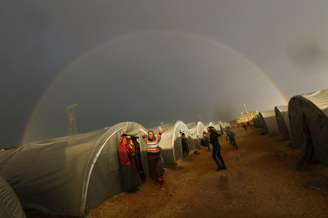 A Kurdish refugee from the Syrian town of Kobani shows victory sign as a rainbow forms over the camp in the southeastern town of Suruc, Sanliurfa province, October 16, 2014. The United States is bombing targets in Kobani for humanitarian purposes to relieve defenders of the Syrian town and give them time to organize against Islamic State militants, a senior U.S. official said on Wednesday. (Photo by Kai Pfaffenbach/Reuters)