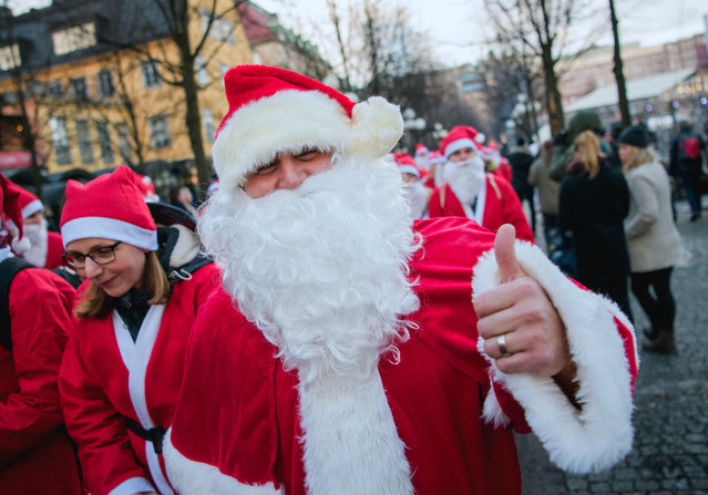 """A charity runner dressed as Father Christmas poses as he participates in the """"Santa Run"""" charity fun run in Stockholm on December 10, 2017. (Photo by Jonathan Nackstrand/AFP Photo)"""