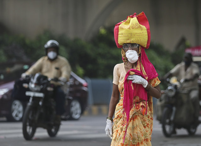 A woman wearing a face mask walks on a street in Hyderabad, India, Friday, July 17, 2020. India crossed 1 million coronavirus cases on Friday, third only to the United States and Brazil, prompting concerns about its readiness to confront an inevitable surge that could overwhelm hospitals and test the country's feeble health care system. (Photo by Mahesh Kumar A./AP Photo)