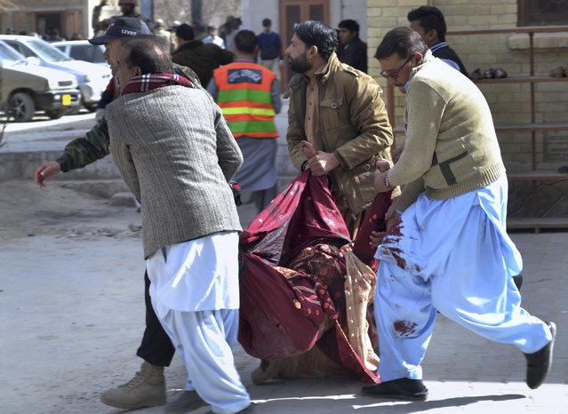 A paramilitary soldier and volunteers rescue an injured women following a suicide attack on a church in Quetta, Pakistan, Sunday, December 17, 2017. Two suicide bombers attacked the church when hundreds of worshippers were attending services ahead of Christmas. (Photo by Arshad Butt/AP Photo)