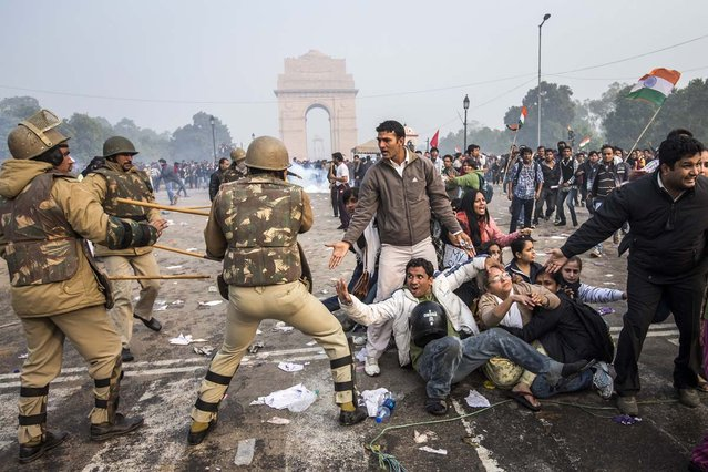 Delhi police lathi charge to disperse protestors during a protest against the Indian governments reaction to recent rape incidents in India, in front of India Gate on December 23, 2012 in New Delhi, India. The gang rape of a 23-year-old paramedical student in a moving bus on December 16, in Delhi, has led to people to react openly against the governments current rape laws. Over a thousand protesters gathered in front of Delhi to protest against lax laws and the governments handling of recent rape cases all over India. (Photo by Daniel Berehulak)