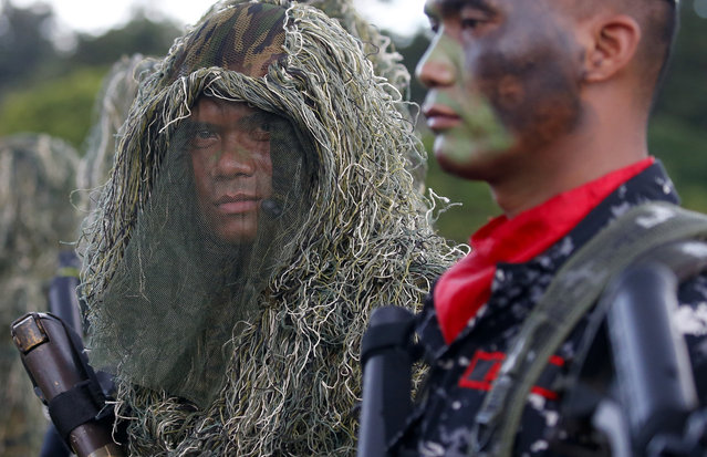 Philippine troops stand at attention during the 82nd anniversary celebration of the Armed Forces of the Philippines in suburban Quezon city northeast of Manila, Philippines Wednesday, December 20, 2017. President Rodrigo Duterte has declared a Christmas truce with communist guerrillas and urged them to reciprocate the goodwill gesture after recently scrapping peace talks with the insurgents and declaring them terrorists. (Photo by Bullit Marquez/AP Photo)