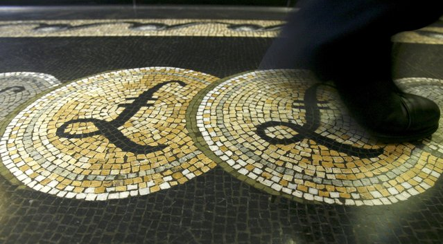An employee is seen walking over a mosaic of pound sterling symbols set in the floor of the front hall of the Bank of England in London, Britain 25, 2008. (Photo by Luke MacGregor/Reuters)