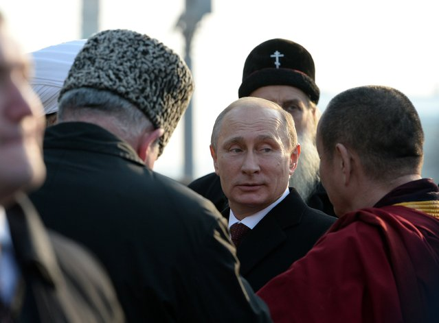 Russian President Vladimir Putin, center, speaks with the confessional leaders during a ceremony at the Red Square in Moscow on Tuesday, November 4, 2014, during the National Unity Day, a national holiday which this year marks the 402th anniversary of the 1612 expulsion of Polish occupiers from the Kremlin. (Photo by Vasily Maximov/AP Photo)
