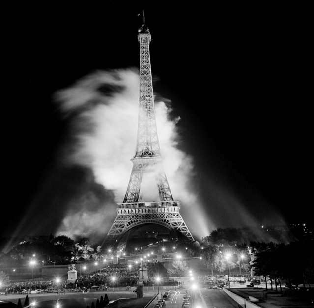 Circled with smoke from a fireworks display, the Eiffel Tower in Paris suggests a missile being launched, October 12, 1962. The giant fireworks show was staged at the tower in connection with a war movie premiere at the nearby Palais de Chaillot. (Photo by AP Photo)