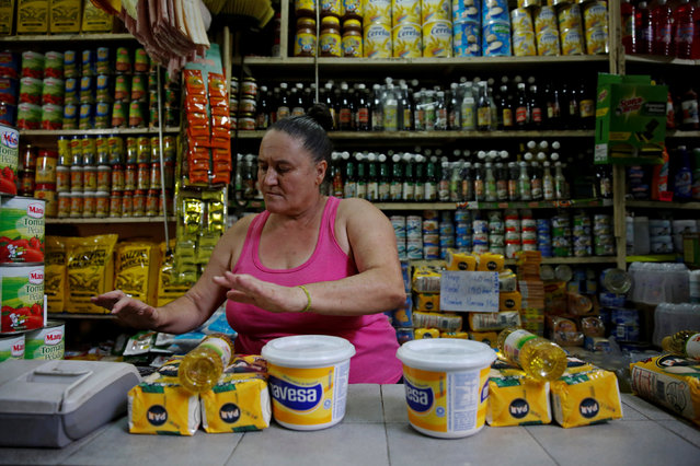 A seller works at her stall during a special inspection of Venezuelan soldiers to a municipal market in Caracas, Venezuela July 15, 2016. (Photo by Carlos Garcia Rawlins/Reuters)