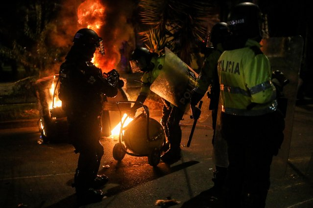 Police officers attempt to extinguish fire from a burning dumpster during a protest after a man, who was detained for violating social distancing rules, died from being repeatedly shocked with a stun gun by officers, according to authorities, in Bogota, Colombia on September 10, 2020. (Photo by Luisa Gonzalez/Reuters)
