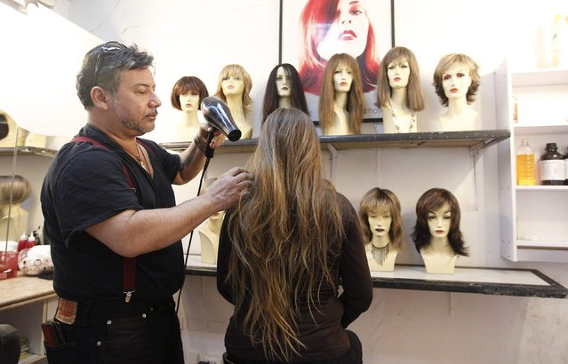 Hair stylist Marcelo Avatte (L) dries the hair of Pamela Matus before she allows him to cut it as a donation for the making of a natural hair wig for a girl undergoing chemotherapy for cancer, in Vina del Mar, August 8, 2014. (Photo by Rodrigo Garrido/Reuters)