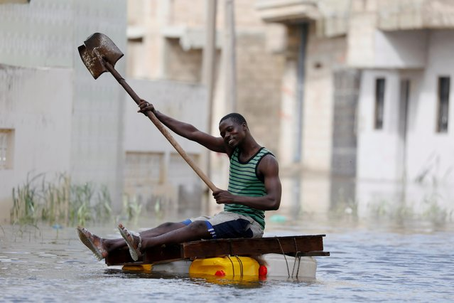 A resident shows his shovel that he uses to row through flooded streets after last week's heavy rains in Keur Massar, Senegal on September 8, 2020. The town on the outskirts of Senegal's capital Dakar remains underwater after a massive downpour, with residents saying some cannot access their homes and that dangerous animals are lurking in the waters. (Photo by Zohra Bensemra/Reuters)