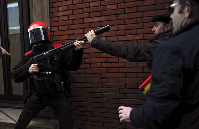 People clash with police during a demonstration to demand jobs for the unemployed, against government austerity measures and alleged corruption of Spanish politicians in front the regional Parliament, in Pamplona, Spain, February 21, 2013. (Photo by Alvaro Barrientos/Associated Press)