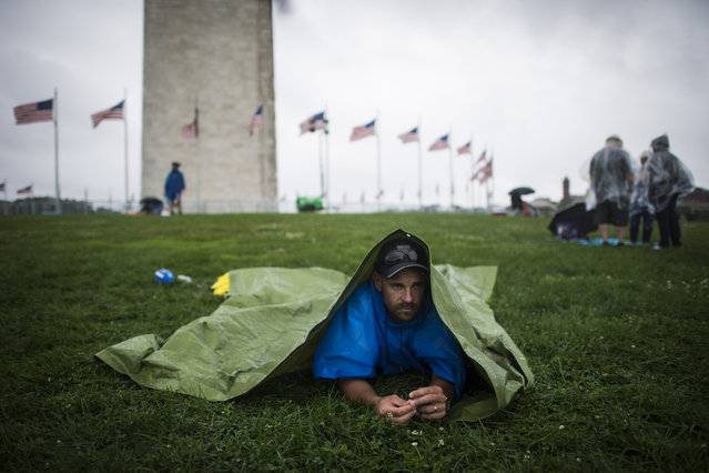 Will Hathaway, hides under a tarp near the Washington Monument as he marks his family's spot as it continues to rain before the Independence Day fireworks on the National Mall in Washington, DC on Monday July 04, 2016. (Photo by Jabin Botsford/The Washington Post)