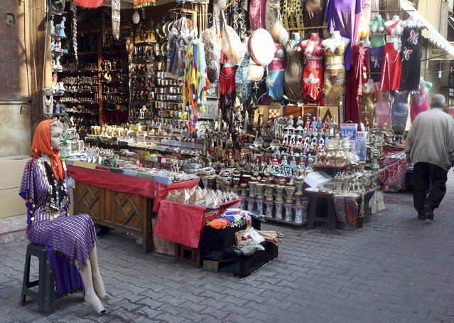 A man walks past a bazaar in Old Cairo November 19, 2014. Once peaking at $12.5 billion a year, tourism revenues were less than half that in 2013 at $5.9 billion as upheaval in the run up to the army's ouster of Islamist President Mohamed Mursi put off foreign visitors. (Photo by Asmaa Waguih/Reuters)