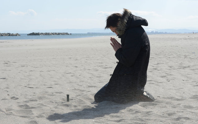 Nobuhisa Iwai prays for his friend killed by the tsunami at Arahama district in Sendai. Japan today marked the second anniversary of the ferocious tsunami that claimed nearly 19,000 lives and sparked the worst nuclear accident in a generation. (Photo by Toru Yamanaka/AFP Photo)