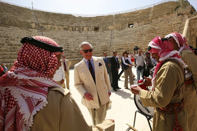 Britain's Prince Charles (C) smiles next to members of a traditional Jordanian troupe as they welcome him during his visit to the ancient Roman ruins in Jerash near Amman March 13, 2013. (Photo by Muhammad Hamed/Reuters)