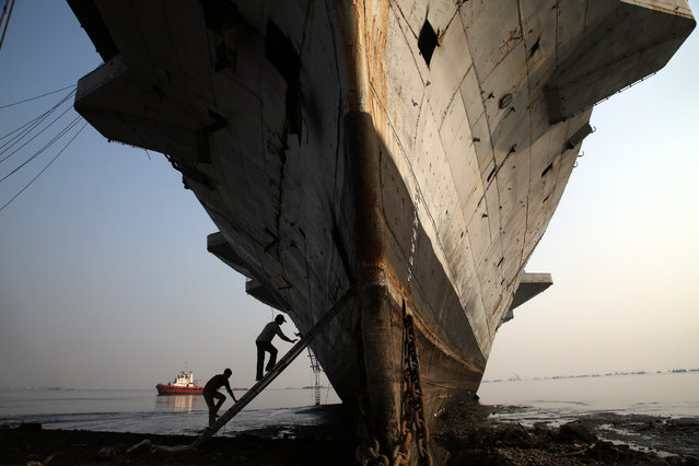 Workers climb to enter India's first aircraft carrier INS Vikrant to dismantle it at a ship-breaking yard in Mumbai, India, Saturday, November 22, 2014. The iconic naval vessel, that was purchased from Britain in 1957, played a key role during the India-Pakistan war of 1971 and was decommissioned in 1997. (Photo by Rajanish Kakade/AP Photo)