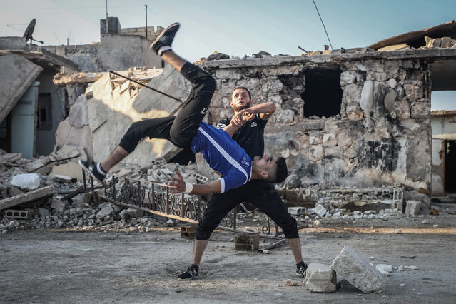 Members of a team comprising Syrian athletes perform parkour stunts amongst the rubble of destroyed buildings in the town of Kafr Nouran, Syria on September 25, 2020. (Photo by Anas Alkharboutli/picture alliance via Getty Images)