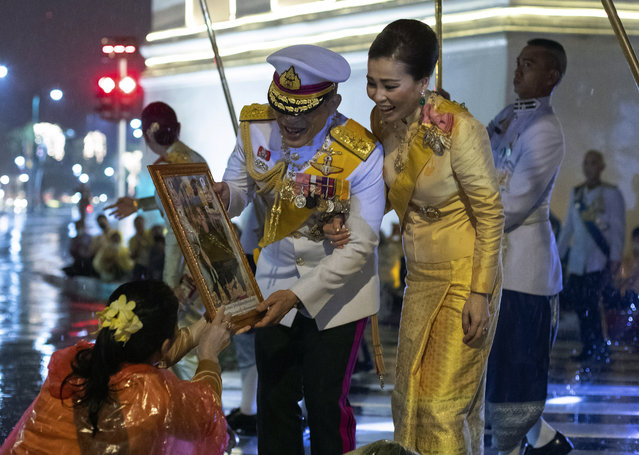 Thai people give a picture of Buddha to Thailand's King Maha Vajiralongkorn and Queen Suthida, as leave the Grand Palace after ceremony marking the fourth anniversary of the death of late Thai King Bhumibol Adulyadej, Bangkok, Thailand, Tuesday, October 13, 2020. (Photo by Wason WanichakornAP Photo)