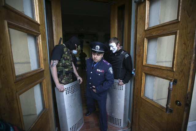 A Ukrainian policeman walks past pro-Russian activists blocking the entrance to a television station in Donetsk, eastern Ukraine, in this April 27, 2014 file photo. (Photo by Baz Ratner/Reuters)