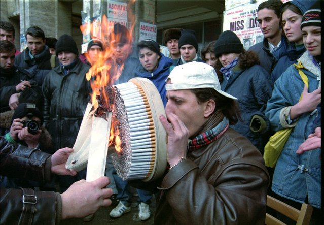 Stefan Sigmund, 29, from the Transylvanian city of Cluj, attempt to smoke 800 cigarettes through a self designed device in less than five minutes, in central Bucharest Tuesday, January 30, 1996, trying to enter the Guinness Book of Records. It is the last of his several attempts entering the record book which included eating 29 hard boiled eggs in four minutes and leaping into a lake from a height of 41 meters (135 feet) even if the Guinness Book of Records no longer rewards self damaging attempts.  (Photo by AP Photo/Stringer)