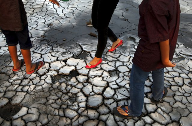 Tourists walk on dried mud at the Lapindo mud field in Sidoarjo, October 11, 2015. (Photo by Reuters/Beawiharta)