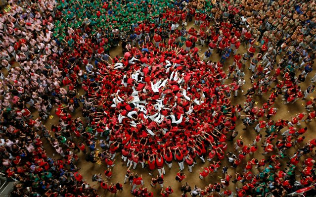 """Colla Joves Xiquets de Valls fall down after forming a human tower called """"castell"""" during a biannual competition in Tarragona city, Spain, October 2, 2016. (Photo by Albert Gea/Reuters)"""